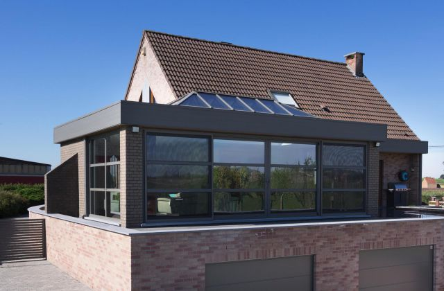 Extension véranda à toiture plate avec puits de lumière. Châssis de couleur gris basalte ( RAL 7012 )