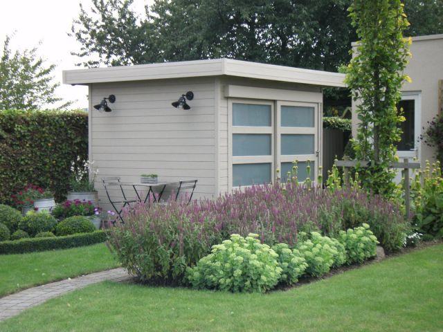 Modern tuinhuis met plat dak en schuifdeur.