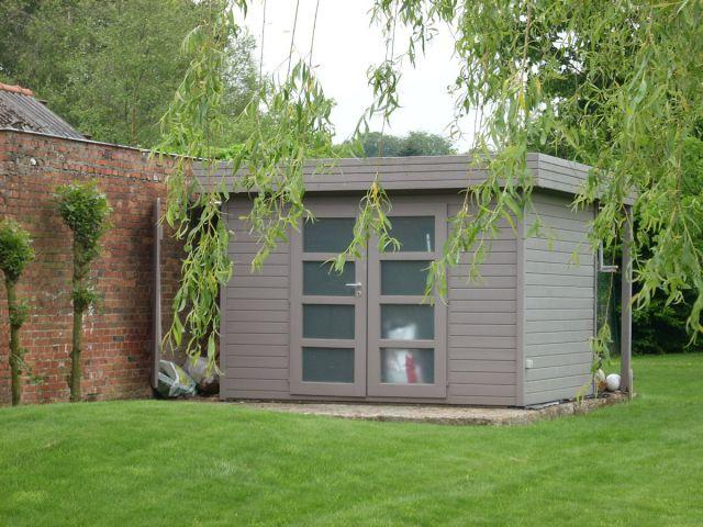 Modern tuinhuis met dubbele deur en een houtstapelplaat aan de achterkant.