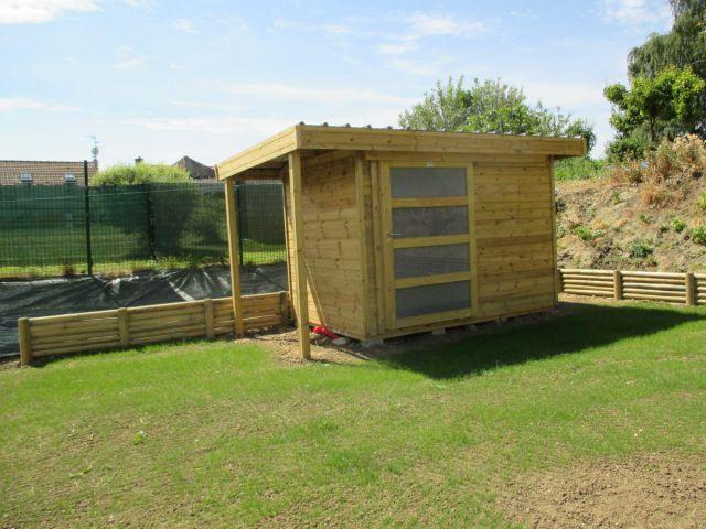 Tuinhuis met plat dak en een houtstapelplaat.