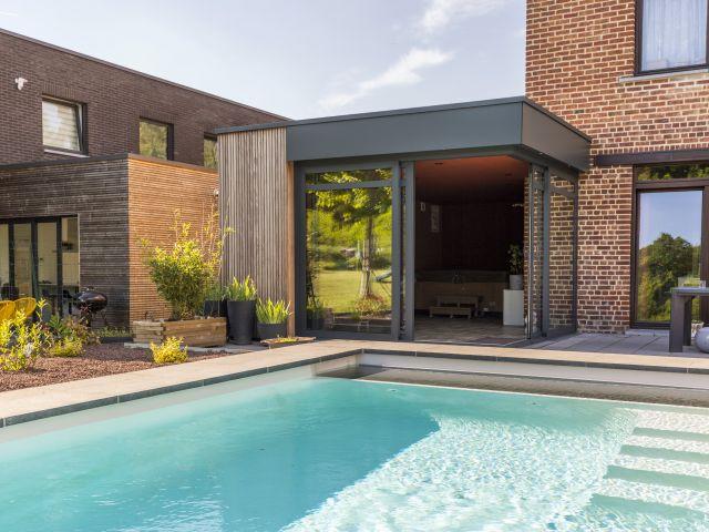 Moderne Woonuitbreiding met Aluminium Ramen, Trespa Panelen en Afrormosia Latten
