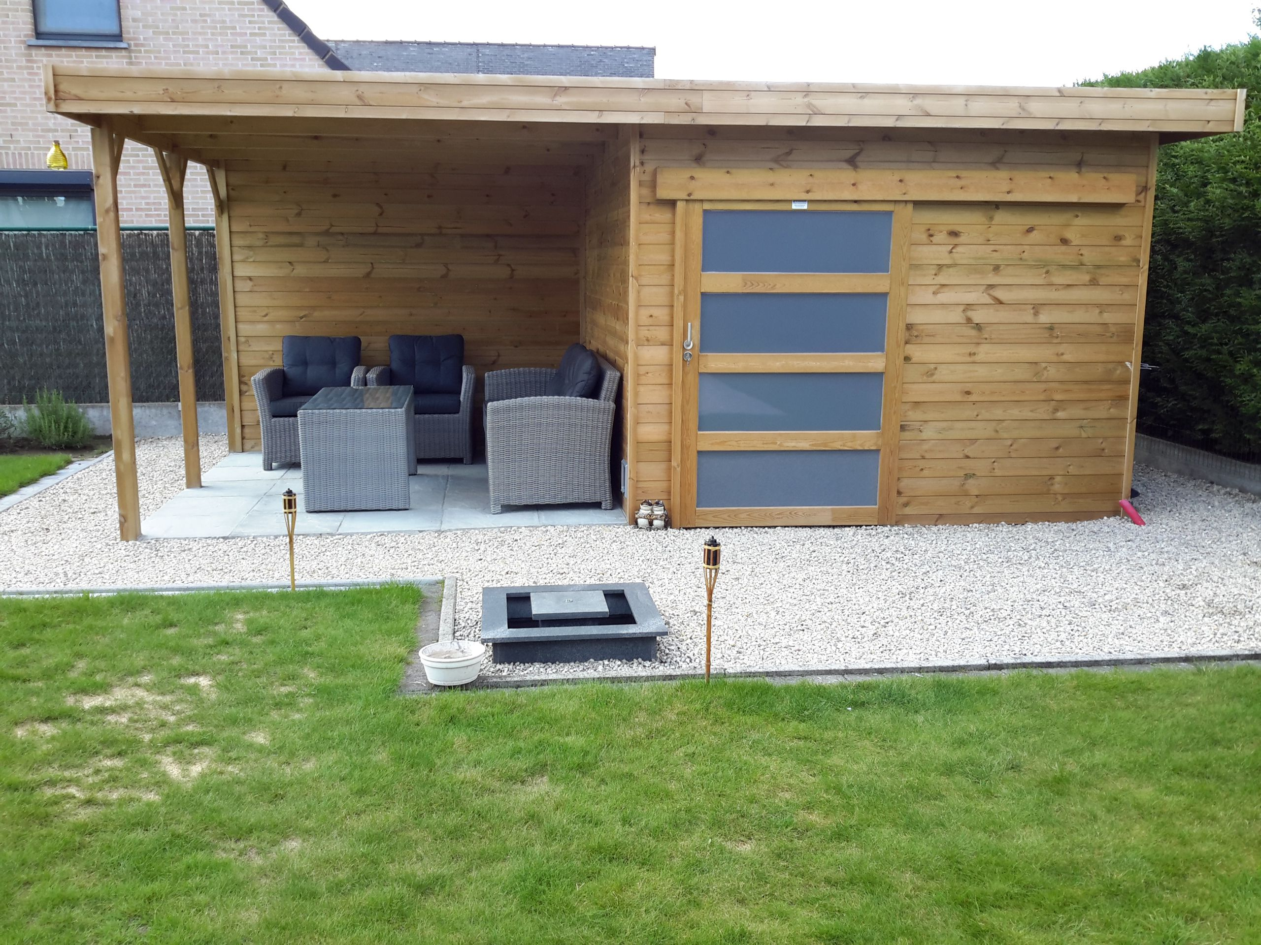 Modern houten tuinhuis met schuifdeur en overdekt terras