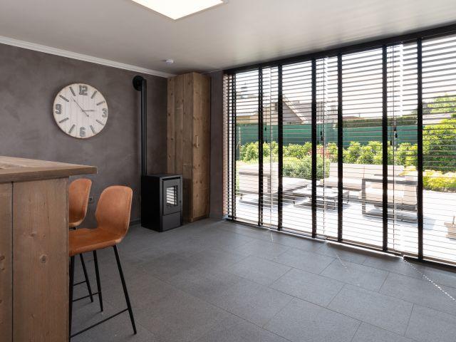 Interieur tuinkamer met bar, schuiframen en kachel