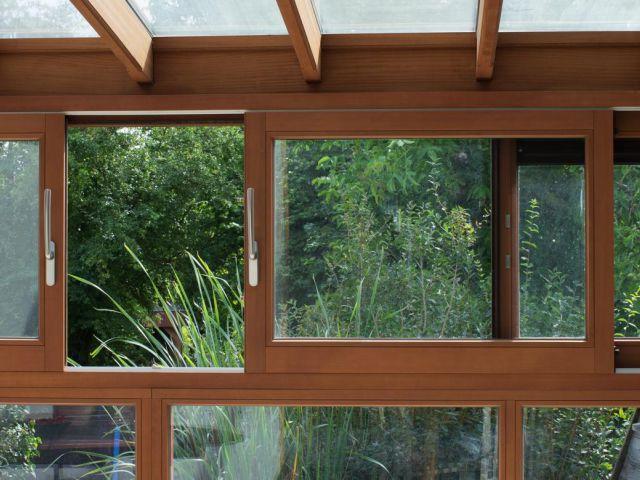 Véranda en bois avec des fenêtres coulissantes