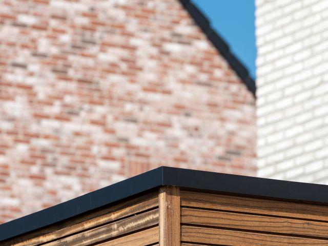 Detail hoek houten pergola in padoek met aluminium afwerkingsprofiel