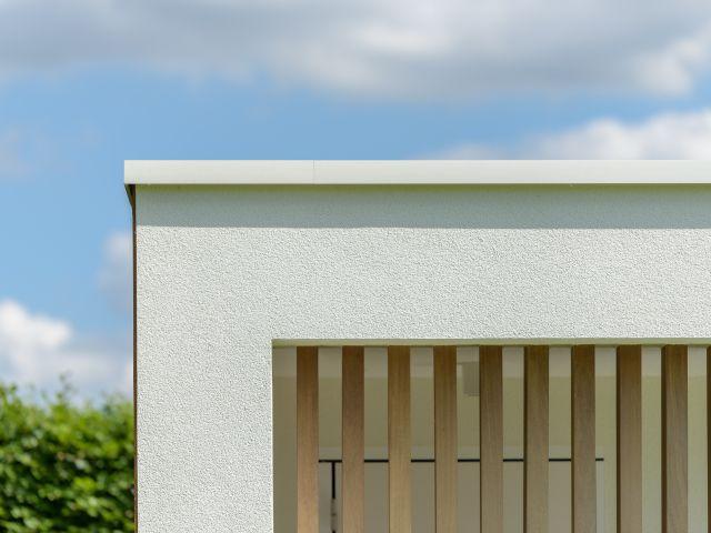 Aluminium dakprofiel bij moderne poolhouse in witte crepi en met irokohout